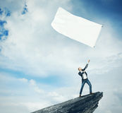 Man with white flag standing on a rock Stock Photography