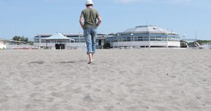 Man with white hat walking barefoot on a beach. Middle aged Caucasian man wearing a white hat relaxing while walking barefoot on a beach stock video footage