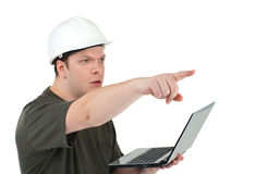 Man in a white helmet with the laptop in hands Stock Image