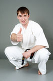 Man in white karate suit. Happy young man in white karate of martial art suit with black belt and thumb up; studio background Royalty Free Stock Photos