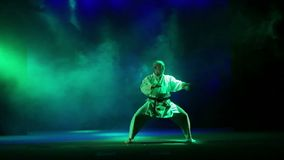 A man in a white kimano is engaged in karate - performs wilderness on the background of colored smoke. HD stock video