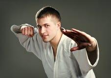 Man in a white kimono. On a gray background Royalty Free Stock Photos