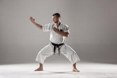 Man in white kimono training karate. Man in white kimono and black belt training karate over gray background Royalty Free Stock Images