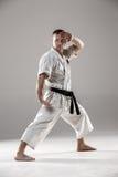 Man in white kimono training karate. Man in white kimono and black belt training karate over gray background Stock Images