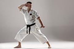 Man in white kimono training karate. Man in white kimono and black belt training karate over gray background Royalty Free Stock Photography