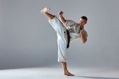 Man in white kimono training karate. Man in white kimono and black belt training karate over gray background Royalty Free Stock Photos