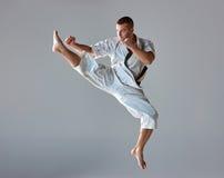 Man in white kimono training karate. Man in white kimono and black belt training karate over gray background Royalty Free Stock Photo