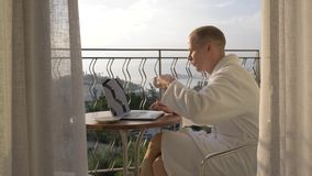 A man in a white lab coat works on a laptop on the terrace overlooking the Bay. 4K stock video footage