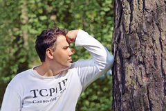 Man in white leans his elbow on tree and thinks Royalty Free Stock Image