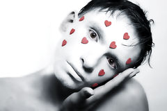 Man with white makeup and red hearts on face Royalty Free Stock Photography