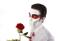 Man with white mascara and bloody shirt holds red rose Stock Photo