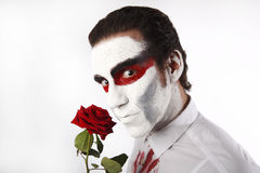 Man with white mascara and bloody shirt holds red rose Stock Image