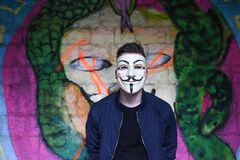 Man in White Mask in Black Crew Neck Shirt and Blue Zip Up Jacket Infront Graffiti Wall Royalty Free Stock Photography