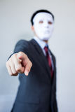 Man in white mask in business suit pointing fingers at something. Royalty Free Stock Photo