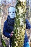 Man with white mask hiding behind tree. Man with white mask hiding behind a tree Stock Photos