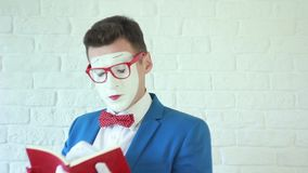 Man in a white mask reading a book stock video footage