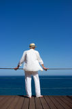 Man in white. Oasis of Calm. Man in white looking at the sea from the terrace. Backward Royalty Free Stock Image