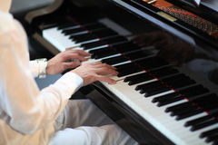 Man in white playing grand piano Royalty Free Stock Image