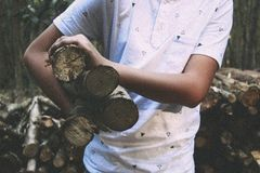 Man in White Polo Shirt Carrying on His Right Firewood Sticks Stock Images