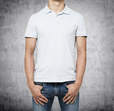 A man in a white polo shirt and denims holds his hands in pockets. Concrete background Stock Images