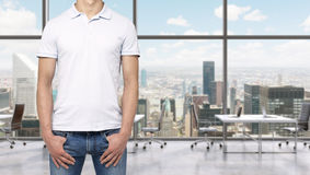 A man in a white polo shirt and denims holds his hands in pockets. A modern panoramic office space in New York City. Royalty Free Stock Images