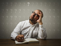 Man in white and question marks. Royalty Free Stock Photo