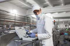 Man in a white robe and a cap make a configure of device stock image