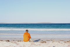 Man at beach looks out over the ocean, Bremer Bay, Western Australia Stock Photo
