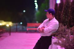 Photo of A man in a white shirt and black pants pensively stands against the urban evening landscape Stock Image