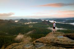 Man in white shirt and black  pants  stand on rock in national park and watch to  beautiful moment Stock Photo