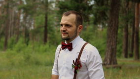 A man in a white shirt with a boutonniere of flowers and greenery. Standing in a beautiful forest. stock video