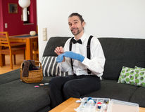 Man in white shirt with bow-tie mending socks. Young bearded man in white shirt with bow-tie mending socks Royalty Free Stock Image
