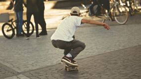 Man in White Shirt and Brown Jeans Riding Skateboard stock images