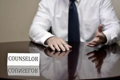 Man in White Shirt at Desk Hands Folded Counselor Royalty Free Stock Photos