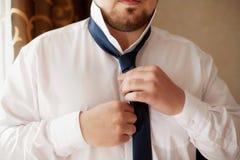 Man in white shirt fixing his black tie, closeup Stock Photos