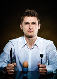Man in a white shirt going to eat an egg Stock Image