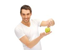 Man in white shirt with green apple Stock Image