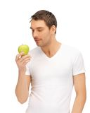 Man in white shirt with green apple Stock Images
