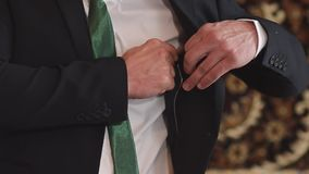 Man in white shirt and green tie, buttoning jacket pocket of the suit, closeup stock footage