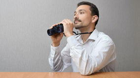 A man in a white shirt is holding binoculars. The person sits thoughtfully at the table. The soneone looks into the distance Stock Photos