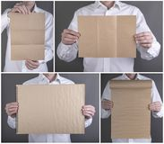 A man holding booklet. A man in a white shirt holding a blank booklet stock photos