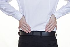 A man in a white shirt holds on to the lower back, back pain, white background, businessman stock photo