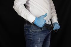 A man in a white shirt and jeans stares into his pants and shows a gesture class, okay, close-up. Erection royalty free stock image