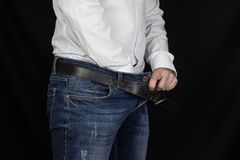 A man in a white shirt and jeans thrust his hand into his pants and holds onto the groin, close-up, black background. Adenoma royalty free stock images