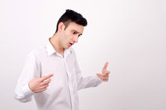 Man in white shirt looking down. Pointing, explaining, gesturing. Young business man looking down gesturing with the hands Royalty Free Stock Images