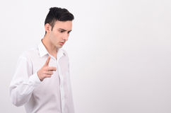 Man in white shirt looking down and pointing the finger. Royalty Free Stock Photos