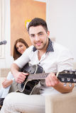Man in white shirt playing guitar and singing Royalty Free Stock Image