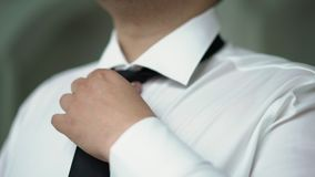 Man put on black tie. Man in white shirt put on black tie stock footage