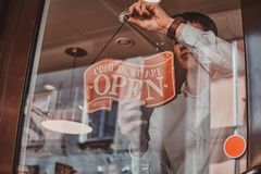 Man is putting nameplate about opening at his own shop. Man in white shirt is putting nameplate about opening at his own shop royalty free stock photos