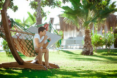 Man in white shirt relaxing in hammock royalty free stock photography